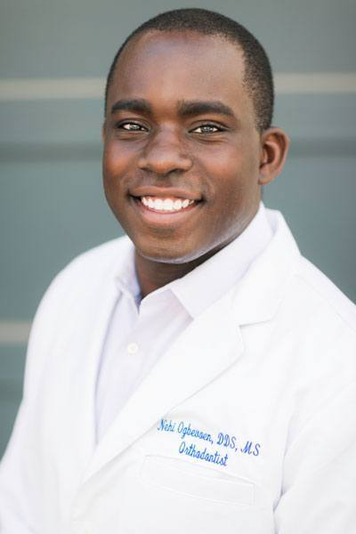 Dr. Ogbevoen wearing a white coat and smiling